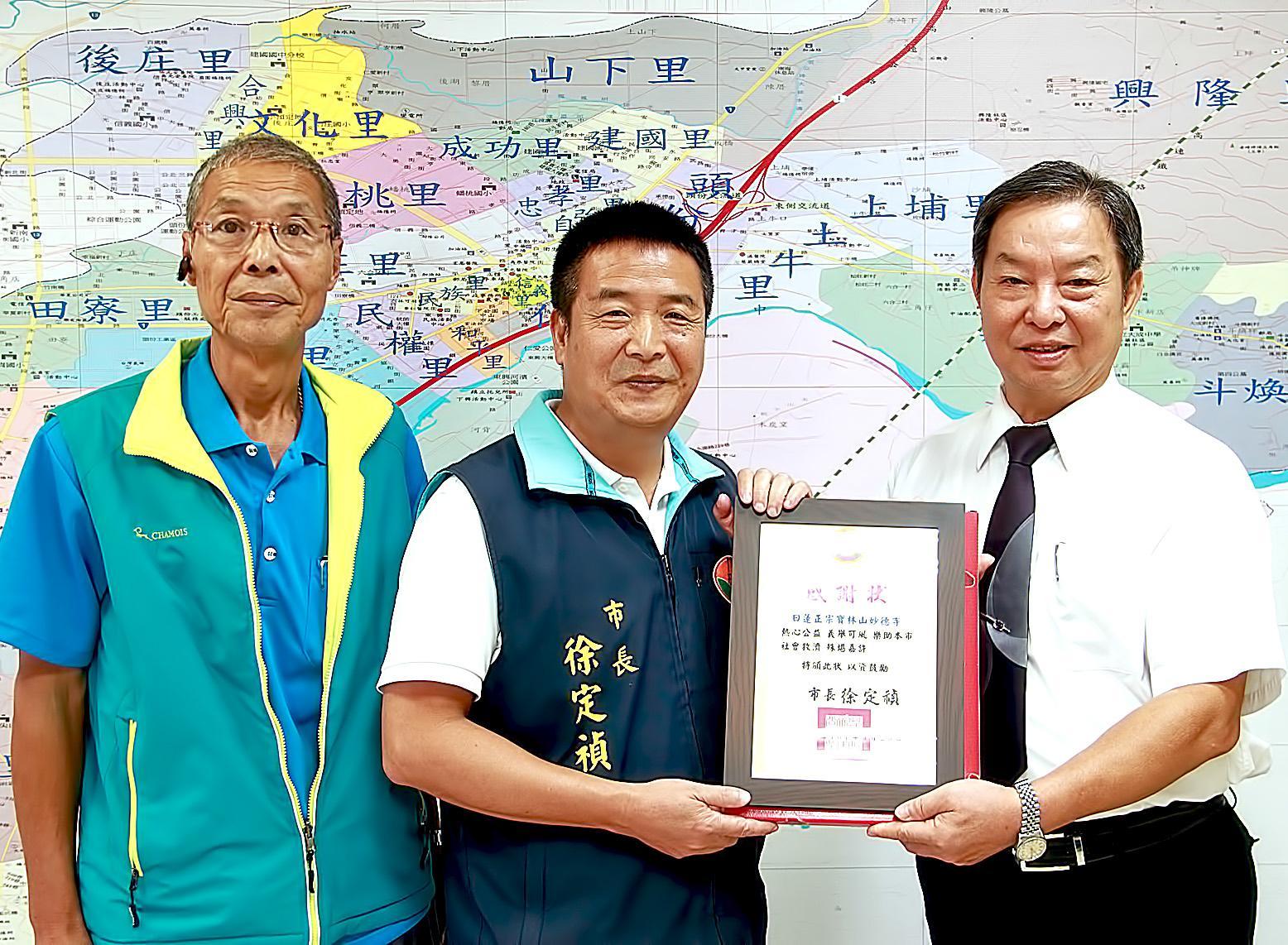 頭份市長徐定禎先生(中)頒發社福貢獻感謝狀,肯定並感謝本基金會竹苗分事務所對地方的貢獻。