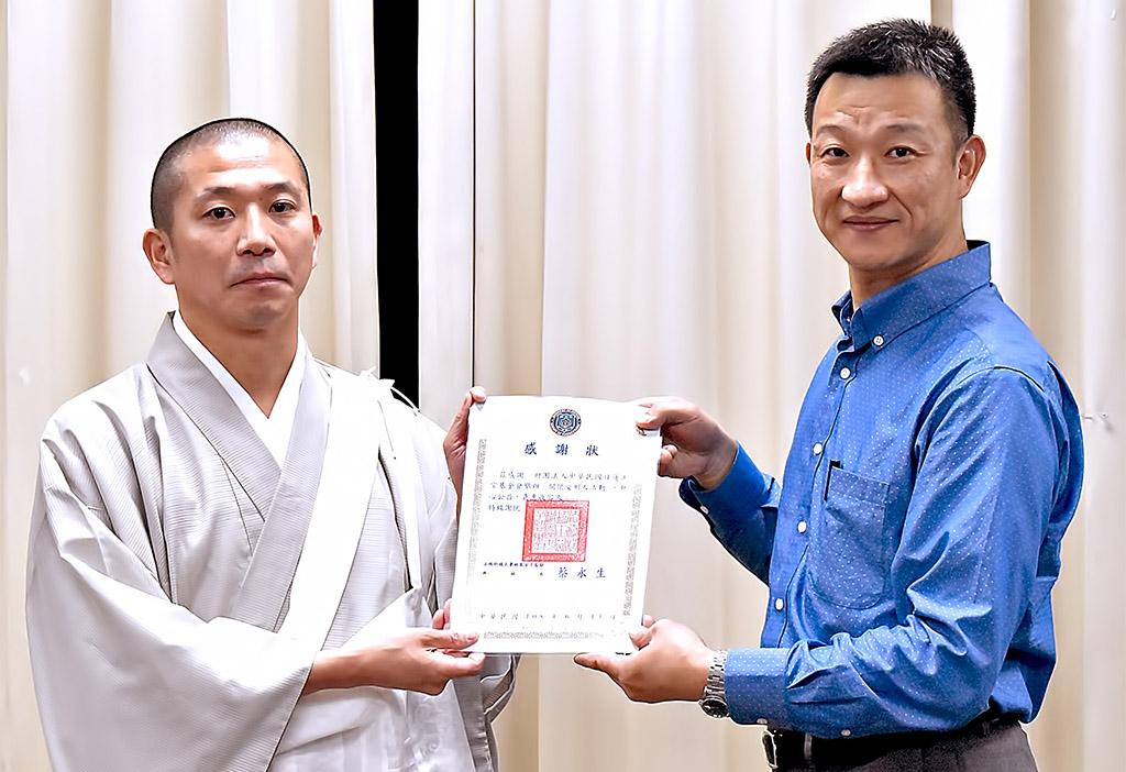 教化科吳紹興科長(右)頒發感謝狀,由關戶執事代表接受。